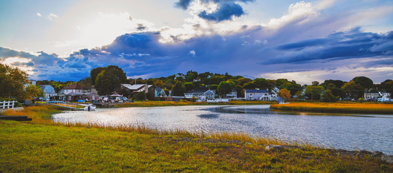 Photo of a city in Massachusetts with homes near the river and grassland surrounding.