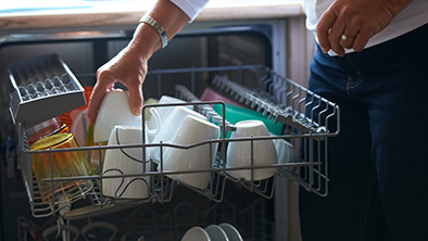 Woman loading white dishes on to the dish washer.