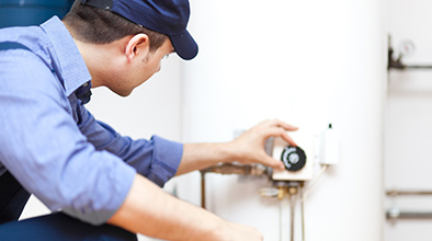 Blue Collar worker adjusting water heater.